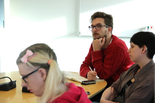 Deltagare på mötet lyssnar när sekreterare Adiam berättar om utredningen.